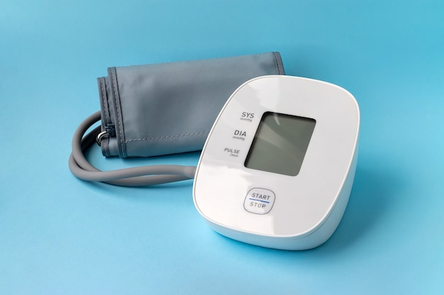 Automatic blood pressure monitor on blue background. medical electronic tonometer