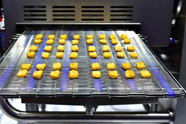 Автоматическая линия по производству куриных наггетсов на конвейерной ленте в промышленном производстве пищевых продуктов