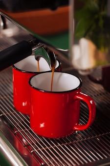 Автоматическая кофемашина готовит два кофе эспрессо в красных винтажных чашках