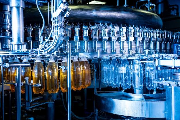 Автоматическая разливочная машина наливает воду в пластиковые бутылки для домашних животных на современном заводе по производству напитков