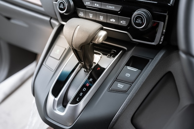 Automatic gear stick of a modern car, car interior details.