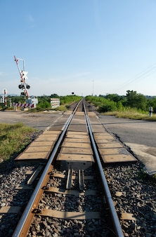 The automatic railroad crossing on the countryside road before the local train station in the northeastern line of thailand, front view with the copy space.
