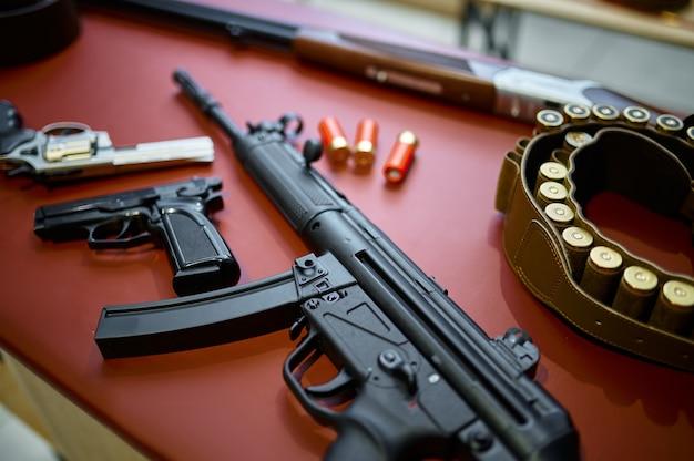 銃店のクローズアップで自動小銃とピストル