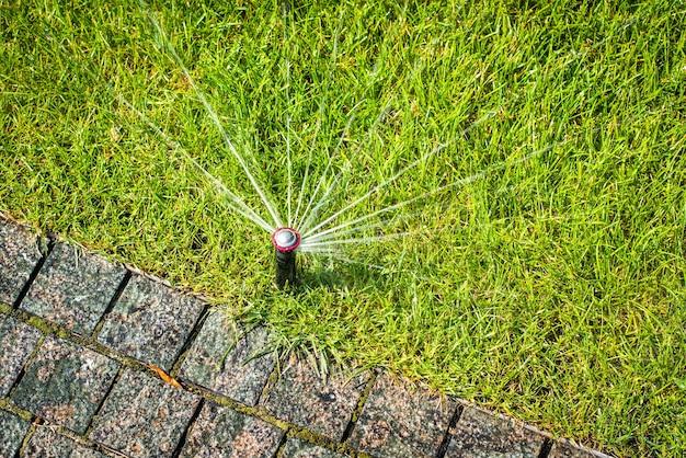 草に水をまくための自動スプリンクラー。芝生は夏に水をまきます。家に便利
