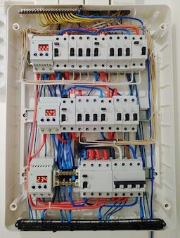 電気シールド内のワイヤーを備えた自動スイッチがクローズアップします。家の中の電気の自動スイッチを備えた電気シールド-回路を備えた電気制御盤。