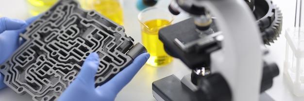 Автоматическая коробка передач лежит в резиновых перчатках на столе с микроскопом и пробирками в крупном плане химической лаборатории. контроль качества концепции моторных масел.