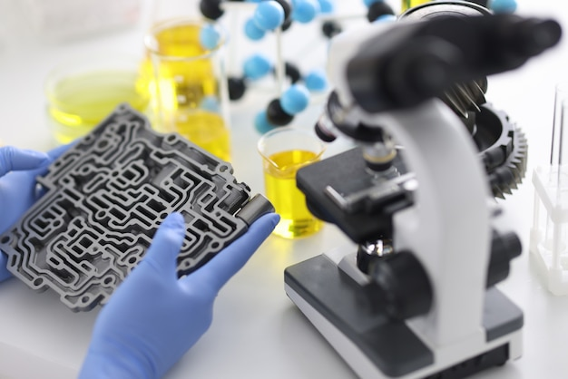 Automatic transmission lies in rubber gloves on table with microscope and test tubes in chemical