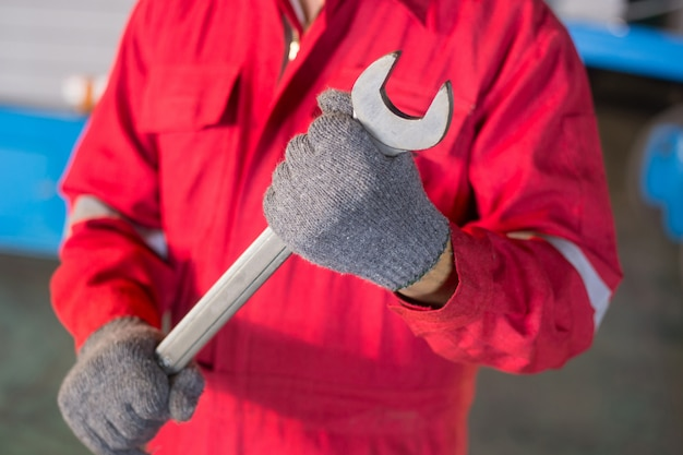 Automechanic in overalls holding wrench or spanner