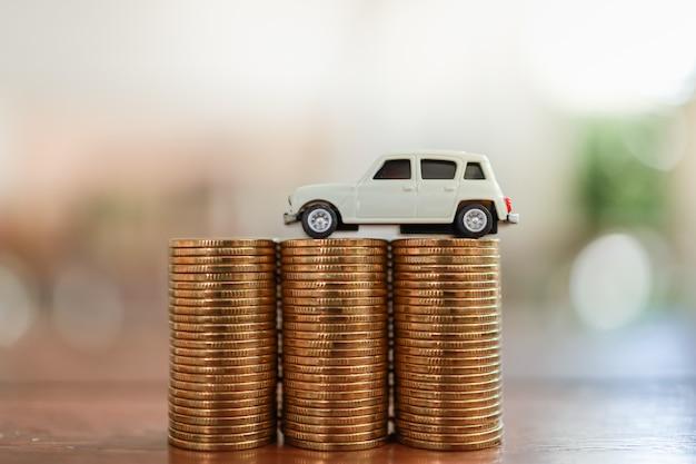 Концепция займа финансов автомобильного бизнеса. закройте вверх белой миниатюрной игрушки автомобиля на стоге монеток с космосом экземпляра.