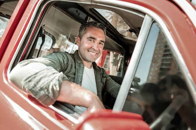 자동차 팬입니다. 쾌활한 남자는 운전대에 앉아 차를 몰고 집으로 가는 창밖을 바라보고 있습니다.
