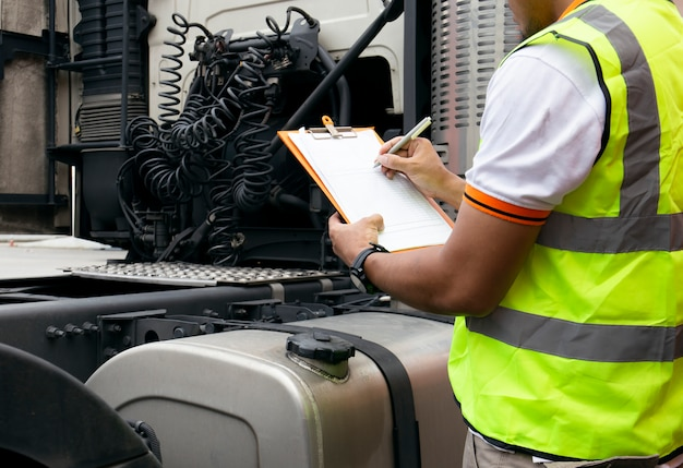 Automobile mechanic are holding a clipboard with checking a truck