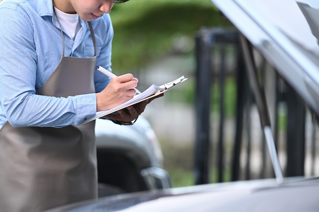 Automobile mechanic is checking a car engine and writing on the clipboard at service station.