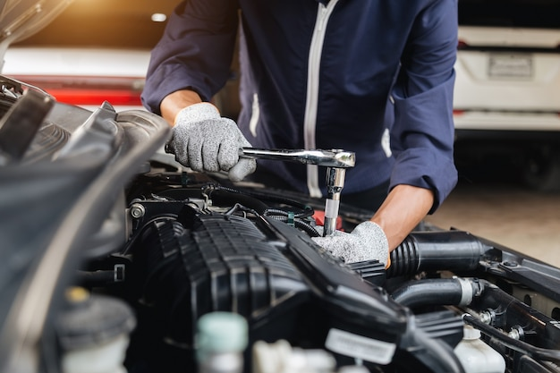 Автомеханик вручает ремонт автомастерской автомобильного двигателя с гаечным ключом, автосервис и техническое обслуживание, ремонтные услуги.