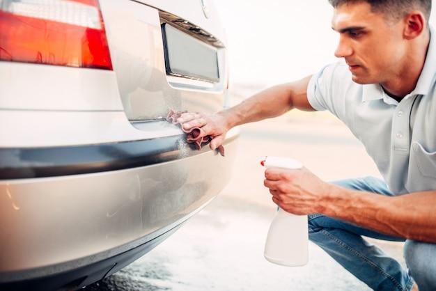 Полировка автомобилей на автомойках. человек протирает бампер автомобиля полиролем.