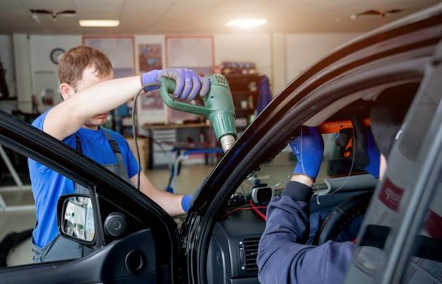 자동차 특수 작업자는 자동 주유소 차고에서 오래된 바람막이 또는 자동차 앞 유리를 제거합니다.