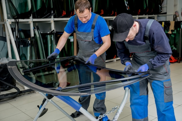 Automobile special workers replacing windscreen of a car in auto service station