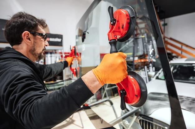 자동차 서비스 스테이션 차고에서 자동차의 앞 유리 또는 앞 유리를 교체하는 자동차 기술자 노동자.