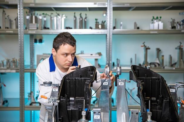 자동차. 품질 엔지니어는 미래의 빛을 위해 플라스틱 주조 측정을 수행합니다.