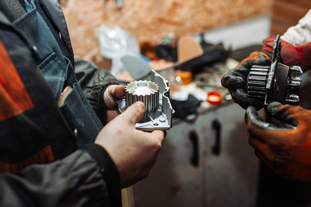 Automotive water pump of the engine cooling system in the hands of an auto mechanic replacement