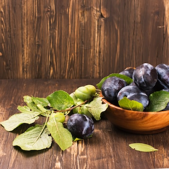 Autum or harvest concept: wooden bowl full of ripe plums.