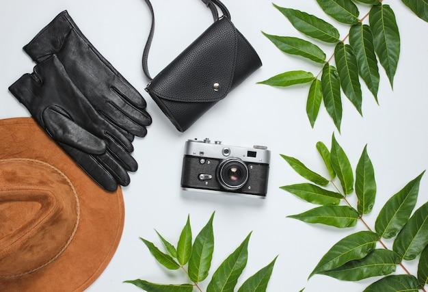 Осенние аксессуары, ретро фотоаппарат на белом фоне с зелеными листьями. войлочная шляпа, кожаные перчатки, сумка. вид сверху