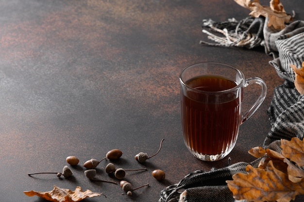 Autumn acorn coffee in cozy lifestyle on brown table with fall oak leaves and cozy scarf. coffee substitute without caffeine. close up. copy space.