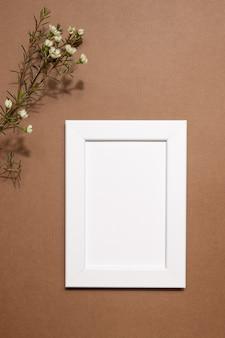 秋の麻酔組成。フォトフレーム、茶色のニュートラルな背景に乾燥した白い花。秋、秋のコンセプト。フラットレイ、上面図、コピースペース上面図