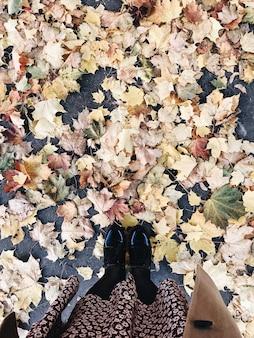 가을과 가을 구성. 검은 부츠, 귀여운 치마 및 말린 단풍에 서있는 베이지 색 코트의 여자