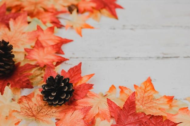 秋と秋のシーズンの背景。木製のテーブルに偽のカエデの葉。宝庫と感謝祭の日のコンセプトを収穫します。
