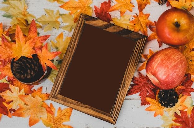 Осенний и осенний сезон. пустая рамка для фотографий и поддельный кленовый лист на деревянном столе. урожай изобилия и концепция день благодарения.
