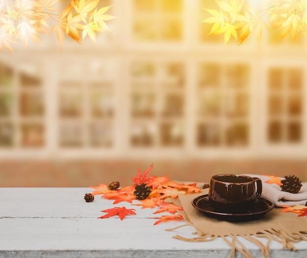 秋と秋のシーズン。木製のテーブルに偽のカエデの葉とホットコーヒー。宝庫と感謝祭の日のコンセプトを収穫します。