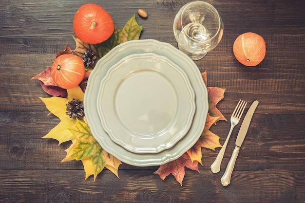 Сервировка стола осени и дня благодарения с опавшими листьями, серым блюдом и серебряными изделиями. вид сверху.