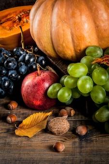 秋と感謝祭の収穫のコンセプト。季節ごとの秋の果物と木製のテーブル、トップビューでカボチャ
