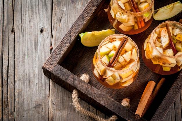 秋と冬の飲み物。暖かいリンゴのサングリア、フルーツ、シナモン、スパイス、砂糖の入ったリンゴサイダー。ガラス、古い素朴な木製のテーブル。食材を使って。