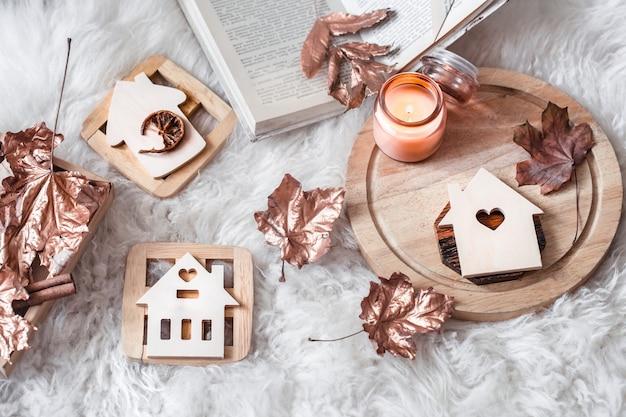 Осенний и зимний домашний натюрморт. вид сверху. деревянные дома с резным сердцем и осенними золотыми листьями.