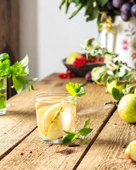 가을 사과 음료, 나무 테이블에 유리에 주스와 민트 사과 조각, 꽃병에 나뭇잎, 마을의 아침, 소박한 개념