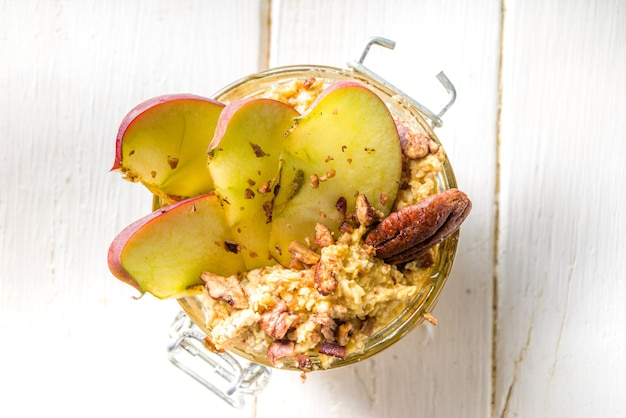Autumn apple pecan oatmeal, overnight oats porridge with red apples, pecan nuts and caramel sauce, white wooden background copy space
