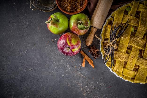 秋のアップルパイ料理の背景。生の伝統的な古典的なアップルパイ、ベーキング材料と道具、黒いコンクリートの背景のコピースペースで背景を焼く