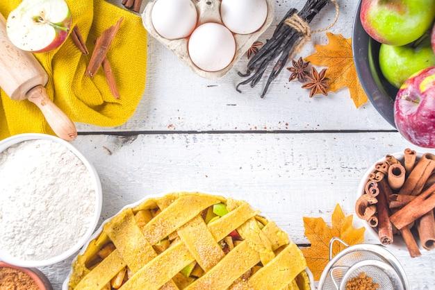 秋のアップルパイ料理の背景。生の伝統的な古典的なアップルパイ、ベーキング材料と道具、白い木製の背景のコピースペースで背景を焼く