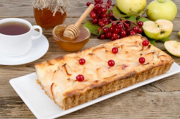 木製のテーブルにガマズミ属の果実と秋のアップルパイ。