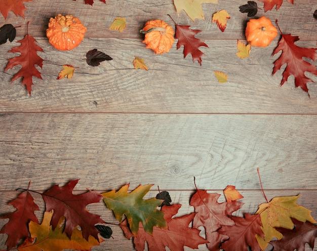 텍스트를 위한 여유 공간이 있는 나무 배경에 화려한 잎, 호박, 도토리, 밤나무 과일의 가을 배열. 상위 뷰, 시즌 개념, 톤 복고 효과, 플랫 레이