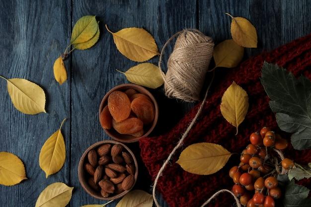 아몬드 말린 살구와 따뜻한 스카프, 짙은 파란색 나무 테이블에 노란색 잎이 있는 가을 배열. 평면도