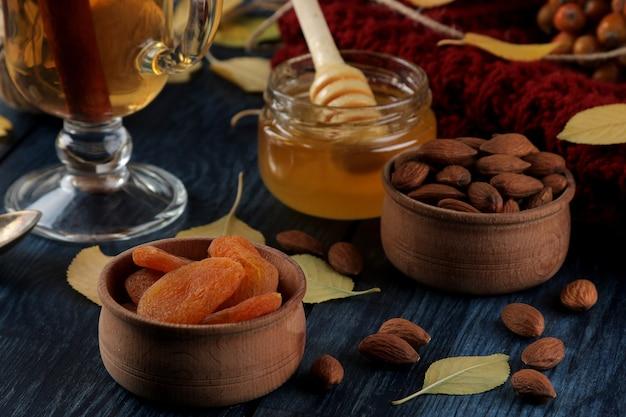 아몬드, 말린 살구, 차, 꿀, 따뜻한 스카프, 짙은 파란색 나무 테이블에 노란색 잎으로 구성된 가을 장식.