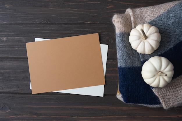 Осенняя композиция с пустой коричневой бумажной тыквой и шерстяным вязанным пледом на деревянном столе