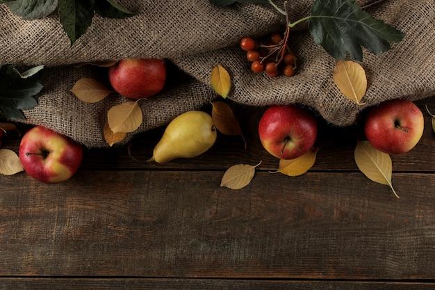 碑文の場所がある茶色の木製テーブルにフルーツリンゴとナシと黄色い紅葉の秋のアレンジメント。上面図