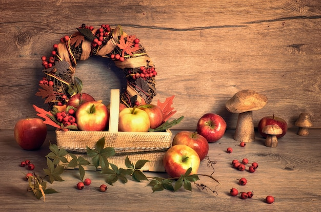 Autumn arrangement with tasty apples, mushrooms and fall wreath