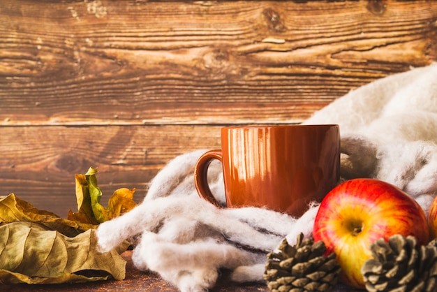 Autumn arrangement with warm scarf and mug