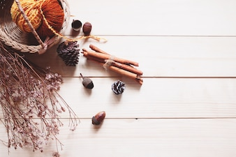 Autumn arrives, knit yarn and dried fruit on wooden table, flat lay with copy space