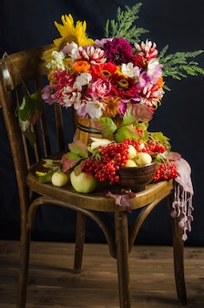 Autumn atmospheric still life with a colorful beautiful bouquet of garden flowers, red berries, apples, autumn leaves on a black surface.