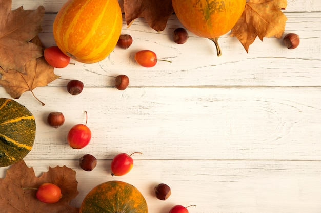 秋の葉のフレーム、ナッツ、黄色と黄色の緑の小さなカボチャと秋の背景